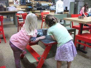 Drawing on the chalk board table tops in the Ride Play Cafe